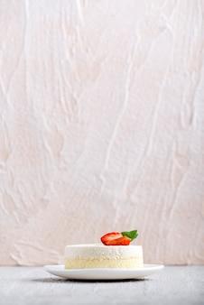 垂直フレーム。明るい背景の上の白いプレートにイチゴとチーズケーキ。側面図。