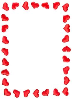 白い背景、バレンタインデーのコンセプトに分離された赤いハートで作られた垂直フレーム。