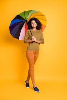 Вертикальная фотография в полный рост жизнерадостной милой вьющейся волнистой очаровательной позитивной подруги в брюках, оранжевой обуви, изолированной на желтом ярком цветном фоне