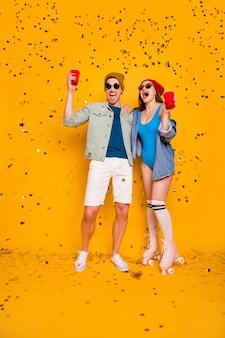 Вертикальный полный размер тела вид на красивый привлекательный веселый веселый рад пара друзей дружба пить пиво досуг отдых расслабиться расслабиться холодный изолированный яркий яркий блеск яркий желтый цвет фона