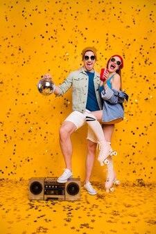 멋진 매력적인 쾌활한 커플 친구 우정 재미 디스코 여가를 마시는 맥주의 수직 전체 길이 몸 크기보기 밝은 생생한 광택 활기찬 노란색 배경