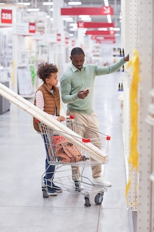 Vertical full length portrait of african-american father and son shopping together in hardware store and using smartphone while choosing wooden boards for home improvement.