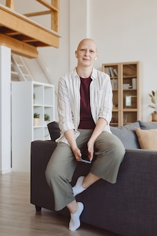 Vertical full length portrait of bald adult woman looking at camera while relaxing casually at home in modern interior, alopecia and cancer awareness, copy space