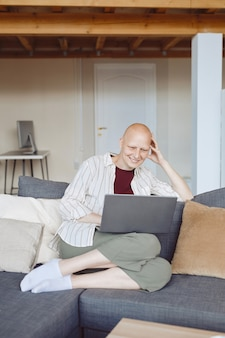 Vertical full length portrait of bald adult woman smiling happily looking at laptop screen while sitting on comfy couch at home, alopecia and cancer awareness, copy space