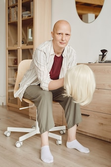 Vertical full length portrait of bald woman holding wig while sitting by mirror and looking at camera in minimal home interior, alopecia and cancer awareness
