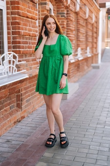 Vertical full length portrait of cheerful young woman talking on mobile phone standing on city street in summer day. joyful happy lady using smartphone outdoors, blurred background, selective focus