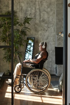 Vertical full length portrait of contemporary tattooed woman with disability listening to music while relaxing at home