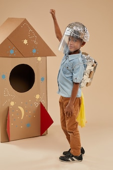 Vertical full length portrait of cute african-american boy playing astronaut in handcrafted space suit while posing on cardboard rocket