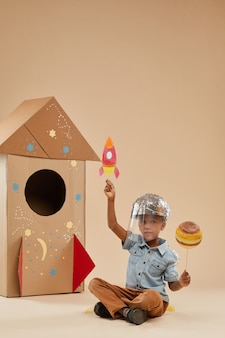 Vertical full length portrait of cute african-american boy playing astronaut in handcrafted space suit while sitting on floor on cardboard rocket