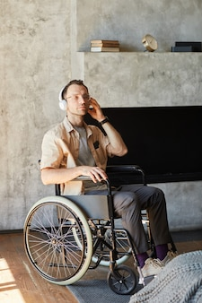 Vertical full length portrait of disabled adult man in wheelchair listening to music at home