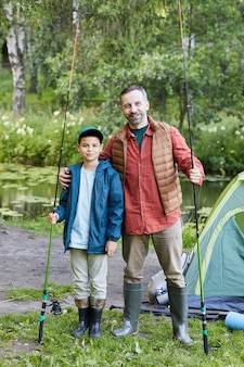 Vertical full length portrait of happy father and son enjoying fishing together and  during camping trip by lake