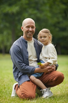 Vertical full length portrait of happy mature father holding cute little daughter while sitting on green grass outdoors enjoying family time in park