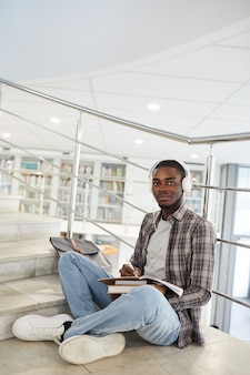 Vertical full length portrait of male african-american student listening to music while sitting cross legged on stairs in college and doing homework,