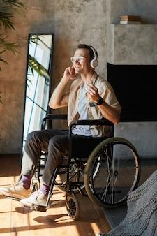 Vertical full length portrait of modern disabled man in wheelchair enjoying music at home