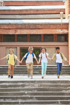Vertical full length portrait of multi-ethnic group of children leaving school with backpacks and holding hands while running towards camera outdoors, copy space