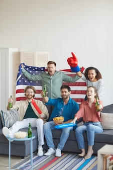 Vertical full length portrait of multi-ethnic group of friends watching sports match on tv and cheering emotionally while holding american flag