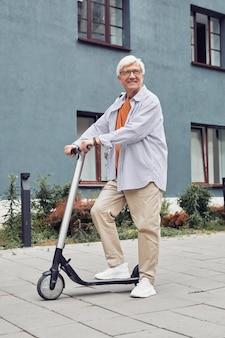 Вертикальный портрет в полный рост активного пожилого человека, катающегося на электросамокате на открытом воздухе и счастливо улыбающегося