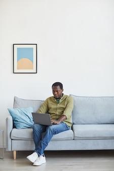 최소한의 가정 내부에서 소파에 앉아 랩톱을 사용하는 성인 아프리카계 미국인 남성의 세로 전체 길이 초상화, 복사 공간