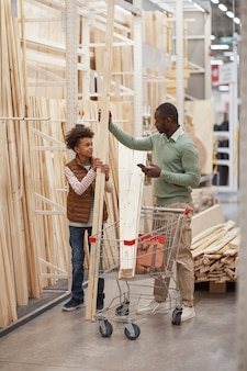 Вертикальный портрет в полный рост афро-американских отца и сына, делающих покупки вместе в строительном магазине, фокус на мужчине, выбирающем деревянные доски для строительства или улучшения дома