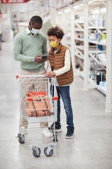 Вертикальный портрет в полный рост афро-американских отца и сына в масках, делающих покупки вместе в супермаркете и проверяющих список покупок на смартфоне