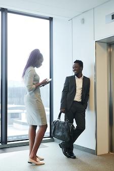 사무실 건물에서 엘리베이터를 기다리고 채팅하는 아프리카계 미국인 남성과 여성의 세로 전체 길이 초상화