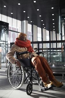 Вертикальный портрет в полный рост афроамериканца в инвалидной коляске, входящего в доступный торговый центр или станцию метро