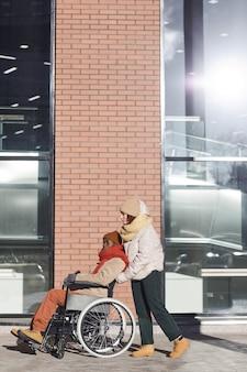 Вертикальный портрет в полный рост афроамериканца в инвалидной коляске, перемещающегося в городском городе с помощью молодой женщины, копией пространства