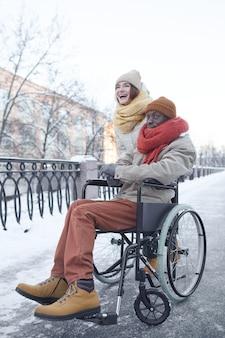 Вертикальный портрет в полный рост афроамериканца, использующего инвалидную коляску, весело проводящего время на открытом воздухе зимой с улыбающейся молодой женщиной и помогающей