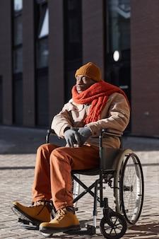 Вертикальный портрет в полный рост афроамериканца, использующего инвалидную коляску в городском городе, освещенном солнечным светом, копией пространства