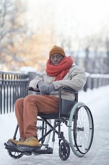 Вертикальный портрет в полный рост афроамериканца, использующего инвалидную коляску на открытом воздухе зимой и смотрящего в камеру
