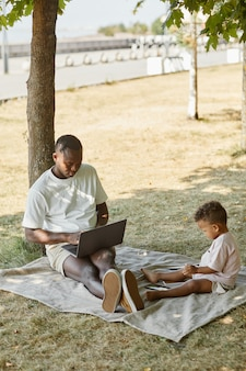 Вертикальный портрет в полный рост афроамериканского отца, использующего ноутбук во время игры с милым сыном в ...