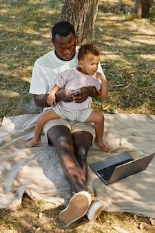 공원에서 야외에서 귀여운 아기와 함께 노트북을 사용하는 아프리카계 미국인 남자의 세로 전체 길이 초상화.