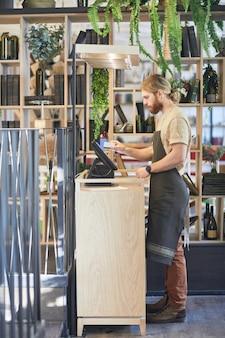 Вертикальный портрет в полный рост бородатого работника кафе, использующего регистр во время обработки заказов в зеленом экологически чистом интерьере