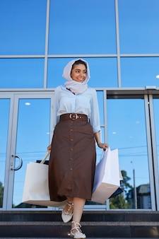 쇼핑 가방을 들고 구매와 함께 쇼핑몰을 떠나는 동안 카메라에 미소 아름다운 중동 여자의 세로 전체 길이 초상화