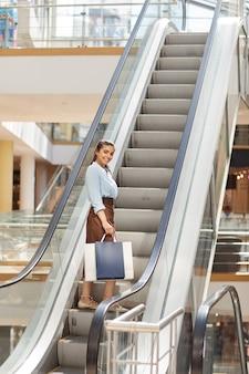 쇼핑몰에서 에스컬레이터에 서서 카메라, 복사 공간에 미소 아름 다운 젊은 여자의 세로 전체 길이 초상화