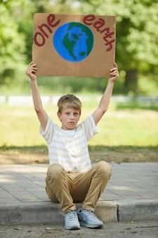 한 지구 기호를 들고 야외 자연을 위해 항의하는 동안 도로 연석에 앉아 금발 십 대 소년의 세로 전체 길이 초상화