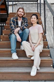 屋外の木製の階段に座って、カメラに笑みを浮かべて現代のカップルの縦長の肖像画