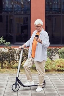 Вертикальный портрет в полный рост современного пожилого человека, катающегося на скутере в городском городе и использующего смартфон