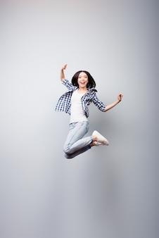 Вертикальный портрет в полный рост сумасшедшей женщины, прыгающей