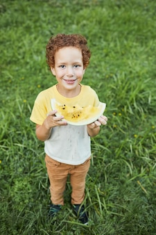 屋外でスイカを保持し、カメラに笑みを浮かべて巻き毛の少年の縦長の肖像画