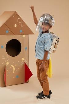 Вертикальный полный портрет симпатичного афроамериканского мальчика, играющего в космонавта в скафандре ручной работы, позирующего на картонной ракете