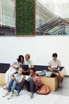 현대 학교 내부 복사 공간에 있는 다양한 어린이 그룹의 세로 전체 길이 초상화