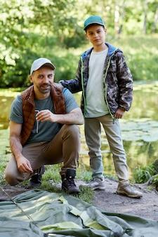 Вертикальный портрет в полный рост отца и сына, устанавливающих палатку и улыбающихся в камеру во время совместного кемпинга у озера