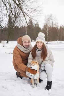 一緒に冬の散歩を楽しみながら屋外で犬とポーズをとってカメラを見ている幸せな大人のカップルの縦長の肖像画