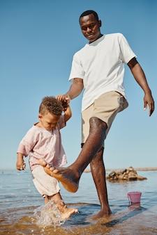 水中でかわいい息子と遊ぶ幸せなアフリカ系アメリカ人の父の縦の完全な長さの肖像画