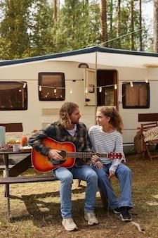 アウトドアキャンプを楽しみながらギターを弾く幸せな若いカップルの縦長の肖像画...