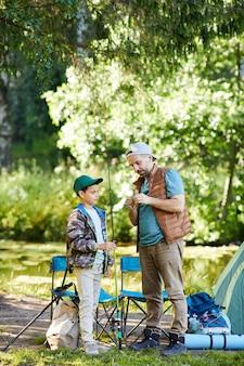 Вертикальный портрет в полный рост любящего отца, который учит сына настраивать рыболовное снаряжение, наслаждаясь вместе в походе