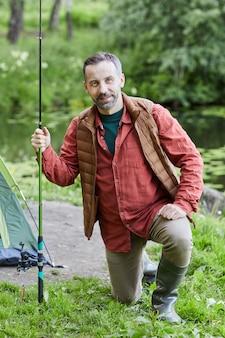 屋外のライフスタイルを楽しみながら釣りとカメラに笑みを浮かべて成熟したひげを生やした男の縦長の肖像画
