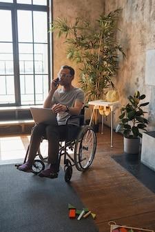 車椅子に座っている間、自宅でラップトップを使用して、障害を持つ現代人の縦長の肖像画、コピースペース