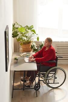 日光に照らされたデスクで自宅で仕事をしながら車椅子を使用している現代の混血の女性の縦長の肖像画、コピースペース